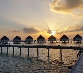 bungalows and ocean at sunset